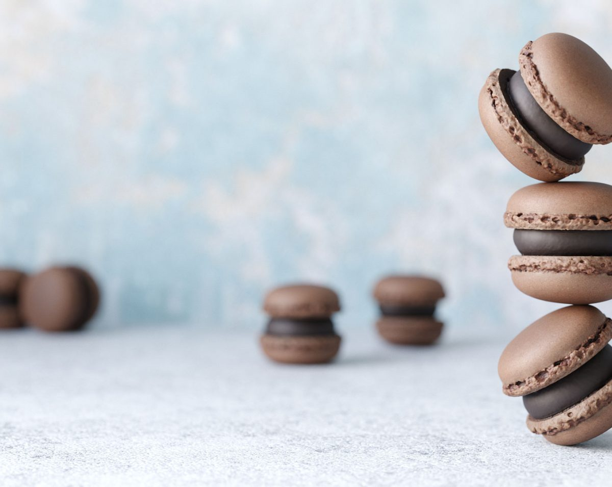 photorealistic close up rendering of a group of chocolate macaron 3d models on concrete